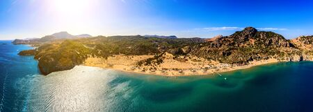 panorama of the famous resort beach tsampika with rows of sunbeds and umbrellas, view of the mountains, the island from a birds eye view, from drone