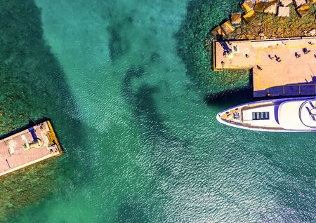 waterfront port of Rhodes Mandraki, clear sea rocky bottom, yachts cars top view from drone