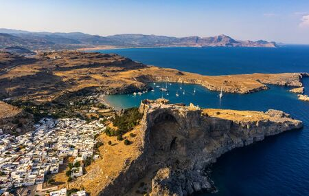 Aerial birds eye view drone photo of village Lindos, Rhodes island, Dodecanese, Greece. Sunset panorama with castle, Mediterranean sea coast. Famous tourist destination in South Europe 스톡 콘텐츠