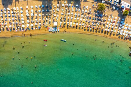 sandy beach with sunbeds and umbrellas, lot of bathing and resting people, view from drone, Greece, Rhodes