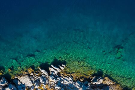 Aerial shot of beach with incredible turquoise colors and rocky cliffs
