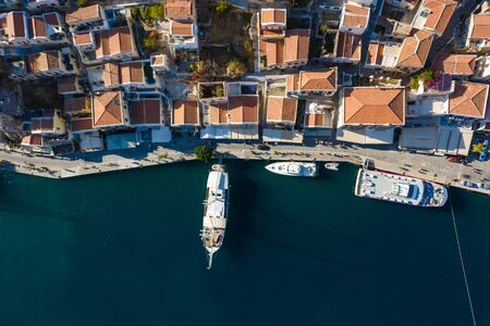 yacht at the Marina of the Bay of Simi island, drone view of the waterfront and houses, Greece, Europe