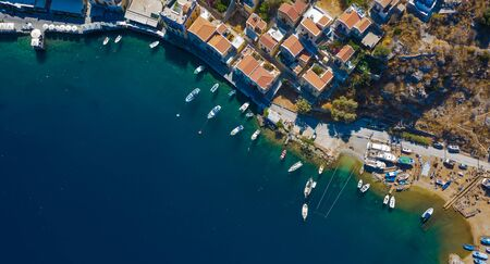 Panoramic view on beautiful Greek houses on island hills, yacht sea port, tourist ferry boat at Aegean Sea bay. Greece islands holiday vacation tours trip