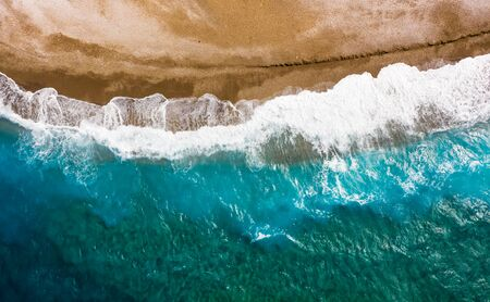 waves of the turquoise sea with blue layers from the sandy shores, the texture view from above with drone