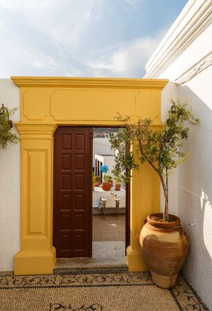 Open door Greek island of Rhodes, Lindos village, pot at the entrance and mosaic of pebbles traditional colorful white house 스톡 콘텐츠