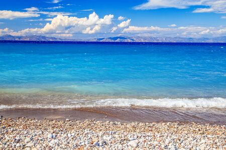 beach view with pebble beach sea, clouds and mountains in the distance, Greek island. 版權商用圖片