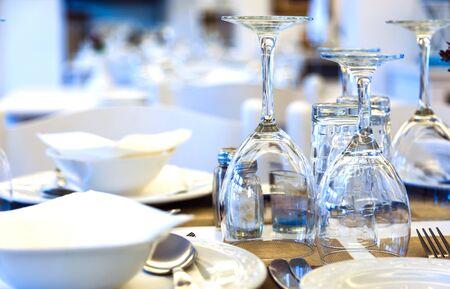 Vasos, platos y cubiertos en la mesa del restaurante en blanco de cerca, restaurante tradicional griego, Europa, Grecia