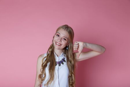 Young beautiful girl shows Dislike , Studio shooting on pink background.