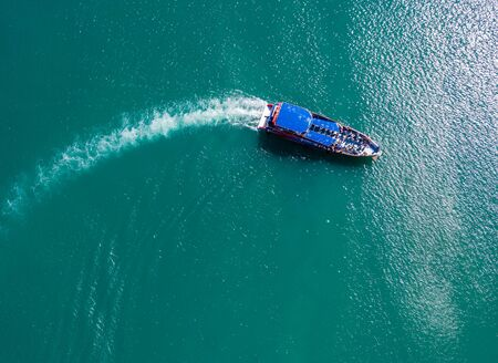 pleasure boat with tourists on Board floating in the sea, the trail with the waves behind, top view from the drone