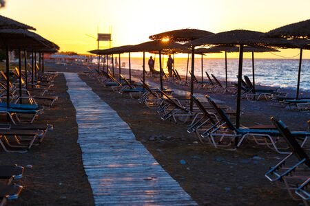 wooden walkway on beach among sun loungers and straw umbrellas at sunset , Greece, Rhodes