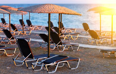 wooden walkway on the beach among sun loungers and straw umbrellas at sunset , Greece, Rhodes