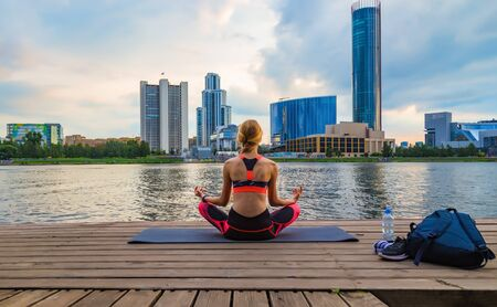 young girl meditates in a yoga pose on the shore of a city pond against the background of modern business buildings. the concept of a healthy lifestyle in the metropolis