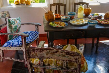 Colorful table and furniture in Sri Lanka Villa, covered with a variety of natural healthy food with fruit on the terrace. Stock Photo