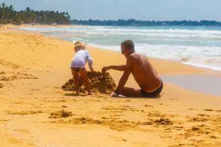 little kid and his father building sandcastle on the sandy shore of a tropical beach, Sri Lanka, ocean waves in the background