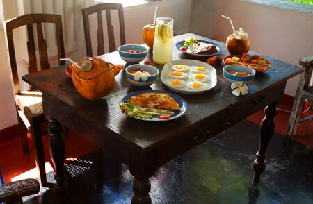traditional natural healthy food on a simple table made of old boards, retro furniture, chairs, pillows, home furnishings on the terrace of an ancient Villa of the 17th century,