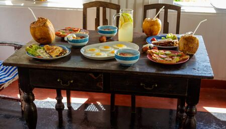 traditional natural healthy food ona simple table made of old boards, retro furniture, chairs, pillows, home furnishings on the terrace of an ancient Villa of the 17th century,