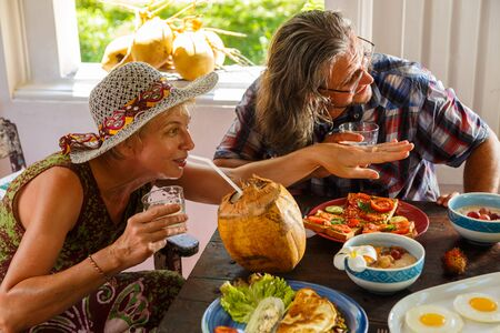 long-haired man and a blonde woman of Caucasian appearance have Breakfast on the veranda of a tropical Villa in Asia, Sri Lanka. Authentic interior, antique wooden furniture
