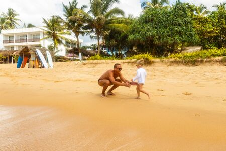 Father throwing his daughter in air at the tropical beach