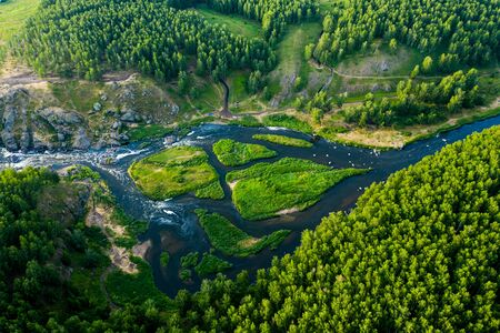 beautiful view vertically down from a great height on beautiful valley with forest and rocks, the mountain river is divided into several streams and Islands. Ural, the threshold Revun.