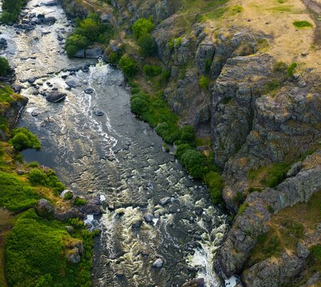 flying on drone over an evening picturesque valley with stormy streams and rapids of the Iset river, tourist places to travel. Ural, Russia