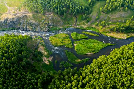 cascade of streams with Islands, green forests and grass, top view from drone, picturesque nature with a mountain river in the forest.