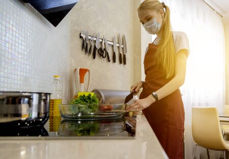 Young woman cooking cocoa biscuit with surgical mask. Stock fotó - 150297013
