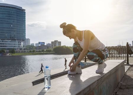 Young modern woman tying running shoes in urban landscape of modern megapolis Stockfoto - 150296853