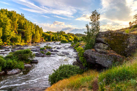 Ural Mountains. Rocks and rocky rifts on a mountain river in summer. View on valley and the river Iset with rocky banks.
