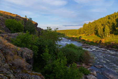 soft sun rays in evening over beautiful valley with a mountain river and many rapids. Ural, Russia, 版權商用圖片