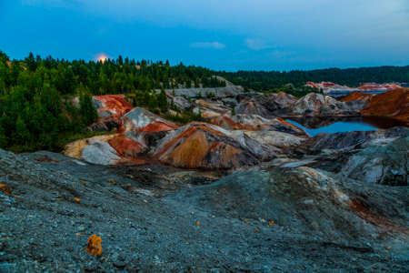 Landscape like a planet Mars surface. Ural refractory clay quarries. Nature of Ural mountains, Russia. Solidified red-brown black Earth surface for screensaver for desktop, banner, cover