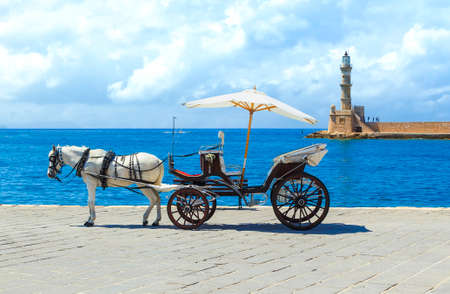 Horse drawn carriages on the quayside with the Venetian lighthouse at the harbour entrance to the rear, Chania, Crete.