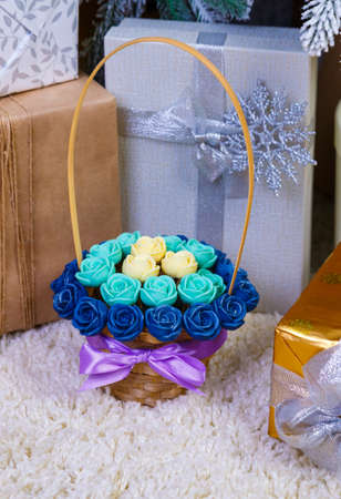 vertical shot basket of chocolate rose flowers among christmas gift boxes