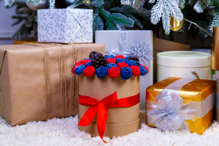 round box with flowers roses made of chocolate under the Christmas tree with white branches among beautiful gift boxes