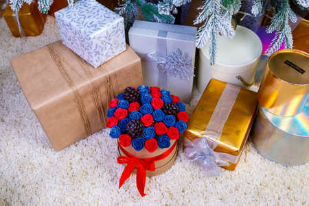 round box with flowers and chocolate cones under a Christmas tree with white branches among beautiful gift boxes on fluffy white rug