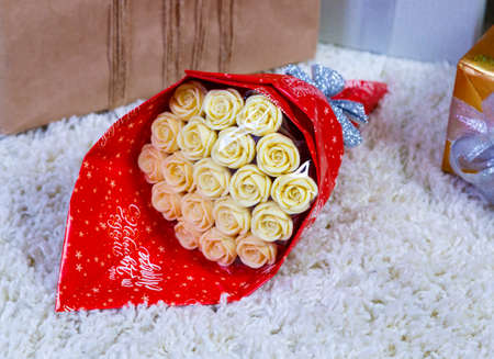 beige roses chocolate flowers wrapped in red film on fluffy white rug among the gift boxes