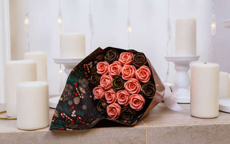 bouquet of chocolate flowers, beautifully packaged, lies on the fireplace among the candles, an unusual edible gift