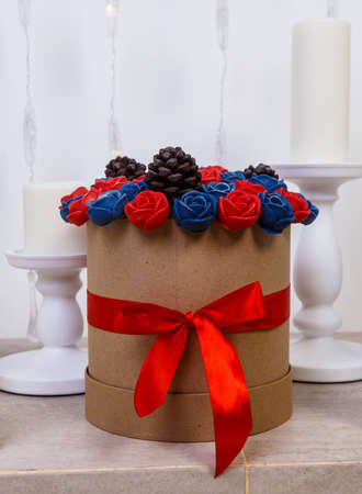 hatbox with bouquet of chocolate roses standing in the fireplace among candles.