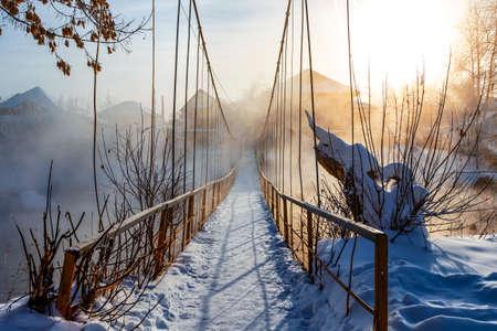 pedestrian bridge over river in the village, fog, severe frost, suspended pedestrian bridge