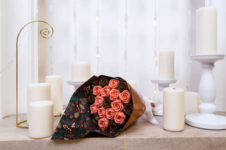 bouquet of roses made of chocolate lies on the marble base of the fireplace among candles. 版權商用圖片