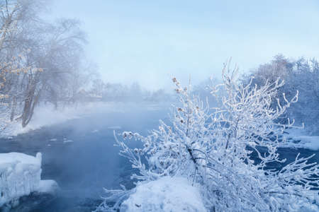 severe frost minus 30 degrees winter Urals, river with fog over it, frozen frost branches