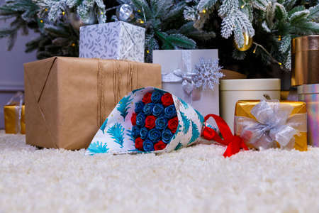 boxes with Christmas gifts under the blue Christmas tree, in foreground a bouquet of chocolate flowers