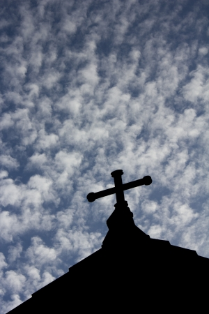 The cross on the church with blue sky and clouds in the background. Stock Photo