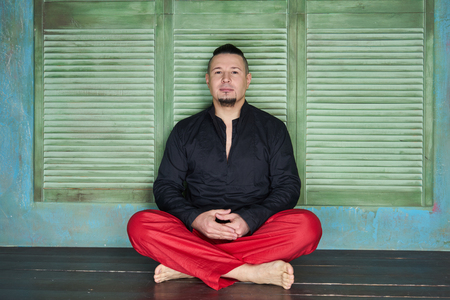 slicked back hair: Portrait of a young man, black shirt and red slacks, hairstyle with shaved temples and slicked- back hair at the top of the head, different emotions, green wall, brown floor, beard, lotus posture Stock Photo