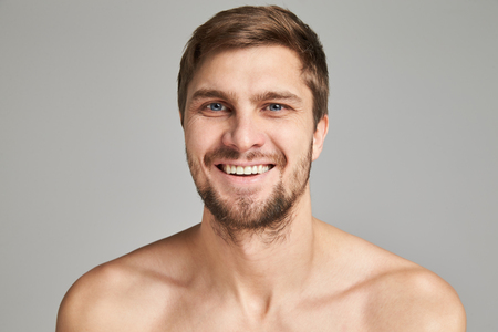 edited photo: Portrait of a smiling young man with bare swimmers shoulders on a gray background, powerful, beard, charismatic, adult, brutal, athletic, edited photo, bright smile, white teeth smile, look in camera