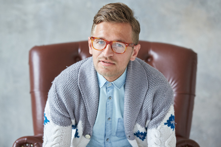 Portrait of a stylish intelligent man with glasses stares into the camera, good view, small unshaven, charismatic, blue shirt, gray sweater, sitting on a brown leather chair