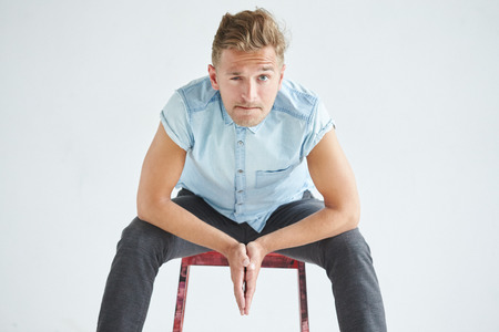 knees bent: Brutal man in a shirt with short sleeves sitting on a red chair , his fists clenched , slightly bent , under the gaze of the forehead, leaned on knees, pensive, listening attentively