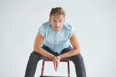 his shirt sleeves: Brutal man in a shirt with short sleeves sitting on a red chair , his fists clenched , slightly bent , under the gaze of the forehead, leaned on knees, pensive, listening attentively