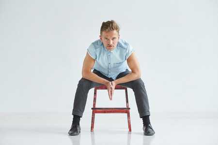 attentively: Brutal man in a shirt with short sleeves sitting on a red chair , his fists clenched , slightly bent , under the gaze of the forehead, leaned on knees, pensive, listening attentively