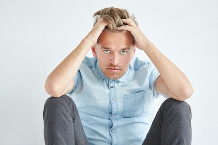 his shirt sleeves: Brutal man in a shirt with short sleeves sitting on the floor, under the gaze of the forehead, holding his head