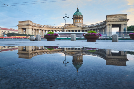 kazanskiy: Russia, Saint-Petersburg, 03 July 2016: Reflection of Kazan Cathedral in a pool on the sidewalk of the Nevsky of the prospectus, after a rain, tourists, sunset, water mirror, long exposure lights